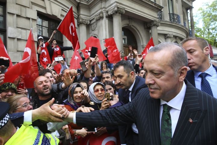 """Turkey's President Recep Tayyip Erdogan shakes hands as his supporters gathered outside his hotel in London, Sunday, May 13, 2018. Erdogan started a three-day visit to Britain by praising the country as """"an ally and a strategic partner, but also a real friend."""" (Presidential Press Service/Pool via AP)"""