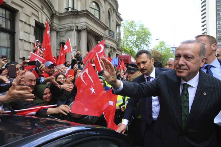 "Turkey's President Recep Tayyip Erdogan, right, waves to his supporters gathered outside his hotel in London, Sunday, May 13, 2018. Erdogan started a three-day visit to Britain by praising the country as ""an ally and a strategic partner, but also a real friend."" (Presidential Press Service/Pool via AP)"
