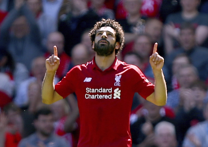 Liverpool's Mohamed Salah celebrates scoring his side's first goal of the game during their English Premier League soccer match against Brighton & Hove Albion at Anfield, Liverpool. England, Sunday, May 13, 2018. (Dave Thompson/PA via AP)