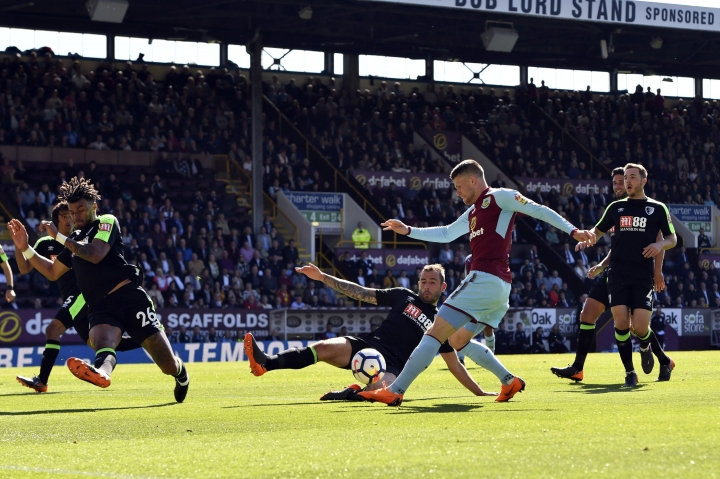 Burnley's Johann Berg Gudmundsson, second right, is tackled by AFC Bournemouth's Steve Cook as he shoots at goal during their English Premier League soccer match at Turf Moor, Burnley, England, Sunday, May 13, 2018. (Anthony Devlin/PA via AP)