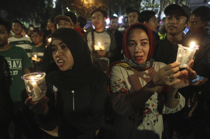 Women hold candles during a vigil for the victims of the church attacks in Surabaya, East Java, Indonesia, Sunday, May 13, 2018. A coordinated suicide bomb attack carried out by members of the same family struck multiple churches on Sunday, police said. (AP Photo/Trisnadi)