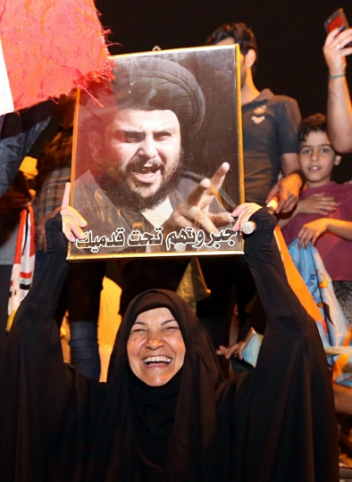 An Iraqi woman holds a picture of Shiite cleric Muqtada al-Sadr as his followers celebrate in Tahrir Square, Baghdad, Iraq, early Monday, May 14, 2018. Iraq's electoral commission announces influential Shiite cleric Muqtada al-Sadr is the current front-runner in national elections with official results in from just over half of the country's provinces. (AP Photo/Hadi Mizban)