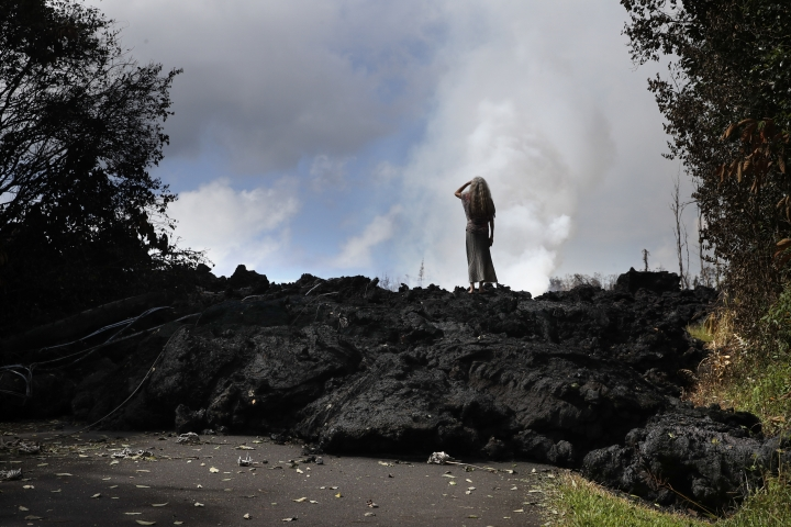 File - In this May 11, 2018 file photo, Hannique Ruder, a 65-year-old resident living in the Leilani Estates subdivision, stands on the mound of hardened lava near Pahoa, Hawaii. The lava hisses, crackles and pops. It roars like an engine as it sloshes and bubbles. It shoots into the sky, bright orange and full of danger, or oozes along the pavement, a giant bubbling blob of black marshmallow-like fluff, crushing homes and making roads impassable. (AP Photo/Jae C. Hong, File)