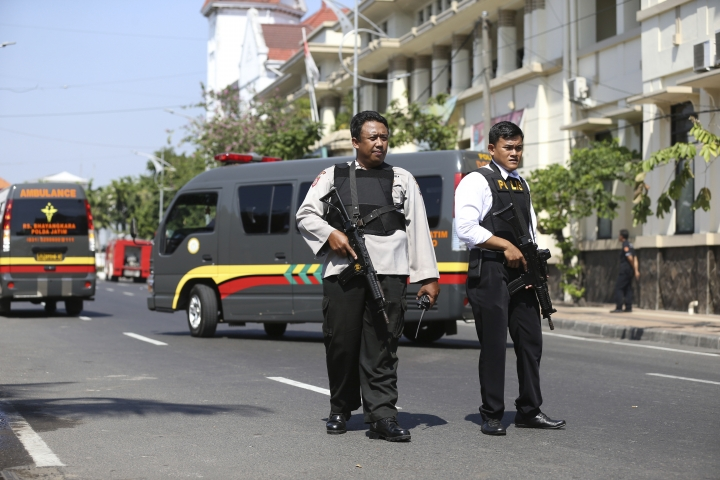 Officers stand guard following an attack at the local police headquarters in Surabaya, East Java, Indonesia, Monday, May 14, 2018. The police headquarters in Indonesia's second largest city was attacked Monday by suspected militants who detonated explosives from a motorcycle, a day after suicide bombings at three churches in the city. (AP Photo/Achmad Ibrahim)