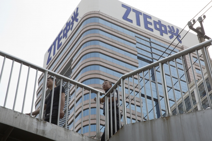 In this May 8, 2018, photo, Chinese men pass by a ZTE building in Beijing, China. President Donald Trump's weekend social media musings about China injected new uncertainty into the Washington's punishment of Chinese tech giant ZTE and planned trade talks between the two countries. (AP Photo/Ng Han Guan)