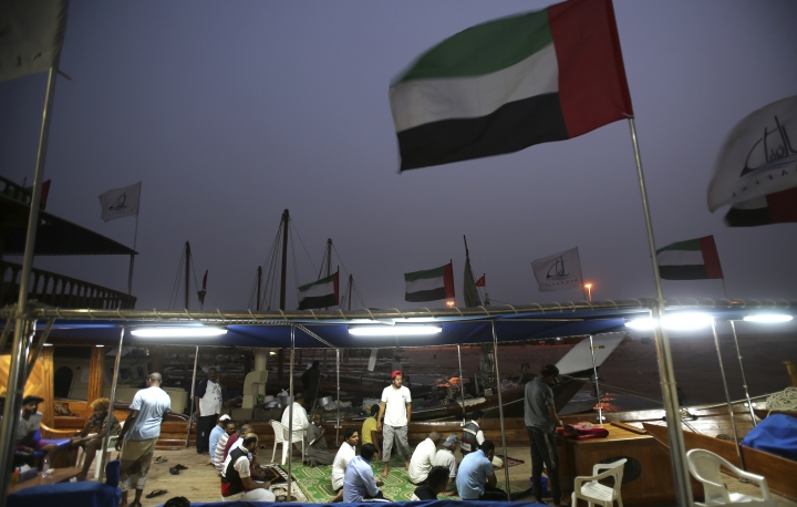 In this Sunday, May 13, 2018 photo, sailors socialize after their evening prayer a day ahead of the Al Gaffal traditional Dhow Race on the island of Sir Bu Nair about 100 kms (66 miles) west of Dubai, United Arab Emirates, Monday, May 14, 2018. (AP Photo/Kamran Jebreili)