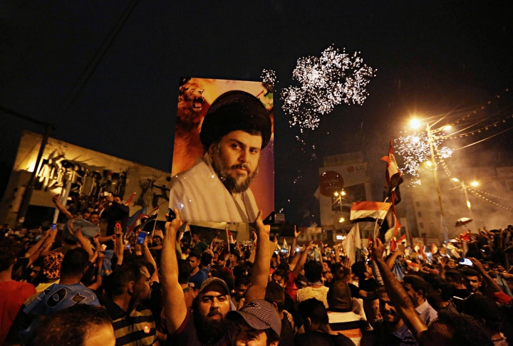 FILE - In this Monday, May 14, 2018 file photo, supporters of Shiite cleric Muqtada al-Sadr, carry his image as they celebrate in Tahrir Square, Baghdad, Iraq. Al-Sadr, who led punishing attacks on American forces after the 2003 U.S.-led overthrow of Saddam Hussein, appears set to secure the most significant victory of his political career with a strong showing in the May 12 parliamentary election. Al-Sadr gained popularity as a nationalist voice campaigning against corruption and against Iran's influence in the country. (AP Photo/Hadi Mizban, File)