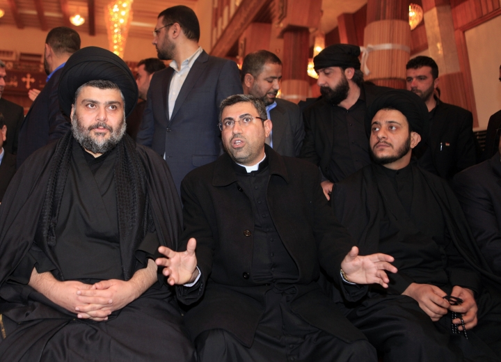 FILE - In this Jan. 4, 2013 file photo, Catholic priest Ayser al-Yas, center, speaks as firebrand Shiite cleric Muqtada al-Sadr, left, visits Our Lady of Salvation church in Baghdad, Iraq. Al-Sadr, who led punishing attacks on American forces after the 2003 U.S.-led overthrow of Saddam Hussein, appears set to secure the most significant victory of his political career with a strong showing in the May 12 parliamentary election. Al-Sadr gained popularity as a nationalist voice campaigning against corruption and against Iran's influence in the country. (AP Photo/ Karim Kadim, File)