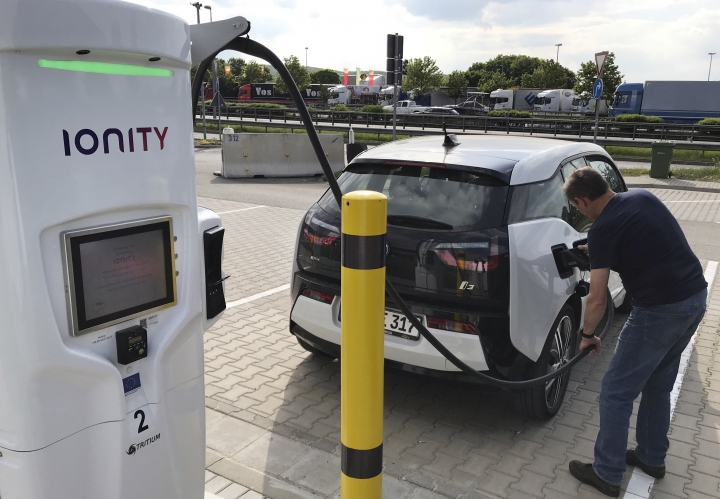 In this Friday, May 11, 2018 photo a man charges his BMW electric vehicle at the rest stop Brohltal Ost at the A61 motorway in Niederzissen, Germany. Munich-based Ionity build a highway network of fast charging stations that will let drivers plug in, charge in minutes instead of hours, and speed off on their way, from Norway to southern Italy and Portugal to Poland (AP Photo/Ferdinand Ostrop)