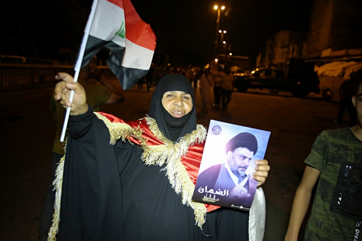 An Iraqi woman holds a picture of Shiite cleric Muqtada al-Sadr during celebrations in Tahrir Square, Baghdad, Iraq, early Monday, May 14, 2018. The political coalition of influential Shiite cleric Muqtada al-Sadr took an early lead in Iraq's national elections in partial returns announced late Sunday by the Iraqi electoral commission. (AP Photo/Karim Kadim)