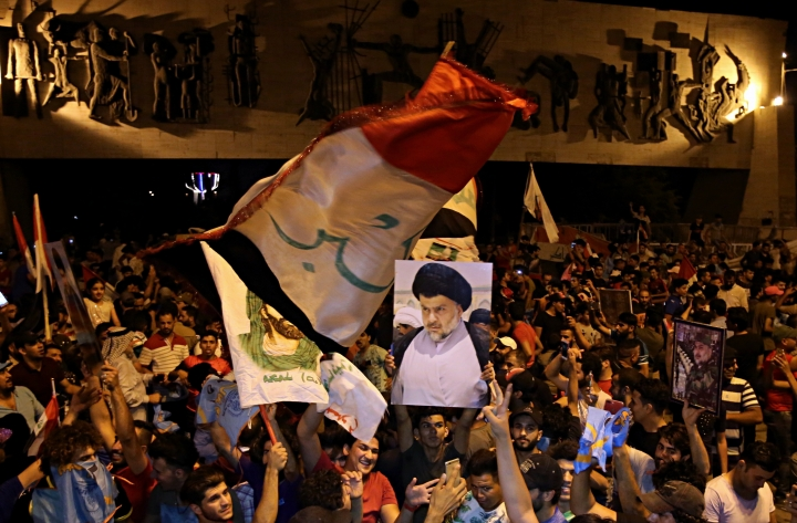 Followers of Shiite cleric Muqtada al-Sadr, seen in the poster, celebrate in Tahrir Square, Baghdad, Iraq, early Monday, May 14, 2018. The political coalition of influential Shiite cleric Muqtada al-Sadr took an early lead in Iraq's national elections in partial returns announced late Sunday by the Iraqi electoral commission. (AP Photo/Karim Kadim)