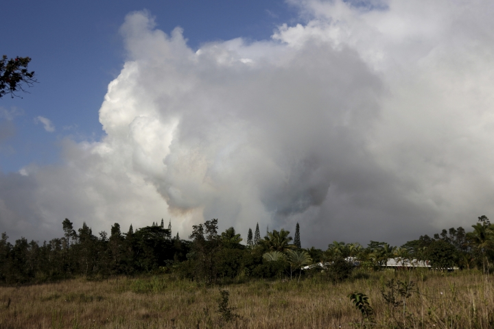 Gases rise from lava fissure 17 after it erupted early Sunday, May 13 2018 near Pahoa, Hawaii.The new fissure emitting steam and lava spatter spurred Hawaii officials to call for more evacuations on Sunday as residents braced for an expected eruption from the Kilauea volcano. (AP Photo/Caleb Jones)