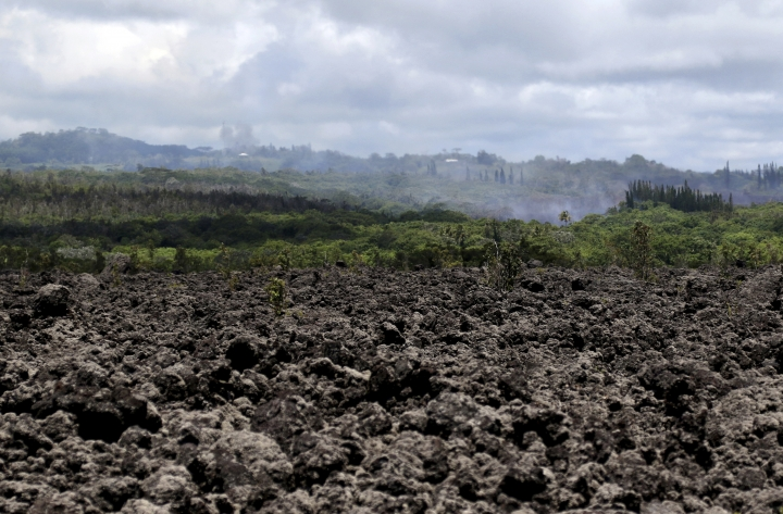 Volcanic gases and ash rise from recent lava fissures near Pahoa, Hawaii on Monday, May 14, 2018. The field of hardened lava rocks in the foreground is from previous eruptions. People nixing vacations to Hawaii's Big island has cost the tourism industry millions of dollars as the top attraction, Kilauea volcano, keeps spewing lava. (AP Photo/Caleb Jones)