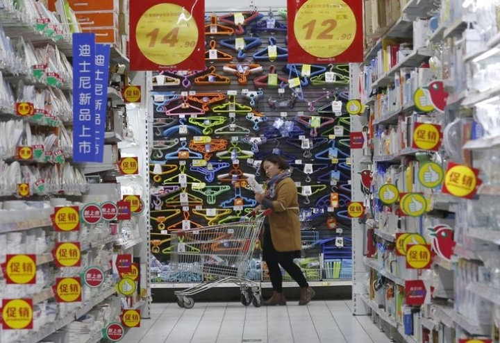 FILE PHOTO: A customer pushes a shopping cart at Sun Art Retail Group's Auchan hypermarket store in Beijing, China, November 9, 2015. REUTERS/Kim Kyung-Hoon