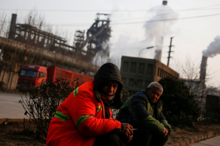 FILE PHOTO: Men sit outside a steel factory in Wu'an, Hebei province, China, February 23, 2017.  REUTERS/Thomas Peter/File Photo