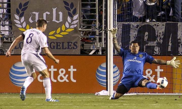 FILE - In this April 23 2016 file photo, Real Salt Lake goalkeeper Nick Rimando, right, tries to save goal by Los Angeles Galaxy midfielder Steven Gerrard in Carson, Calif.. Australia's Luongo was one of four outfield players unused by coach Ange Postecoglou in the Socceroos squad that went out in the group stage of the 2014 World Cup. The soccer teams at upcoming World Cup have 23 potential players in the squad, but some players never make it off the bench, they are the unused spares who still need to be motivated for the good of the team. (AP Photo/Ringo H.W. Chiu, File)