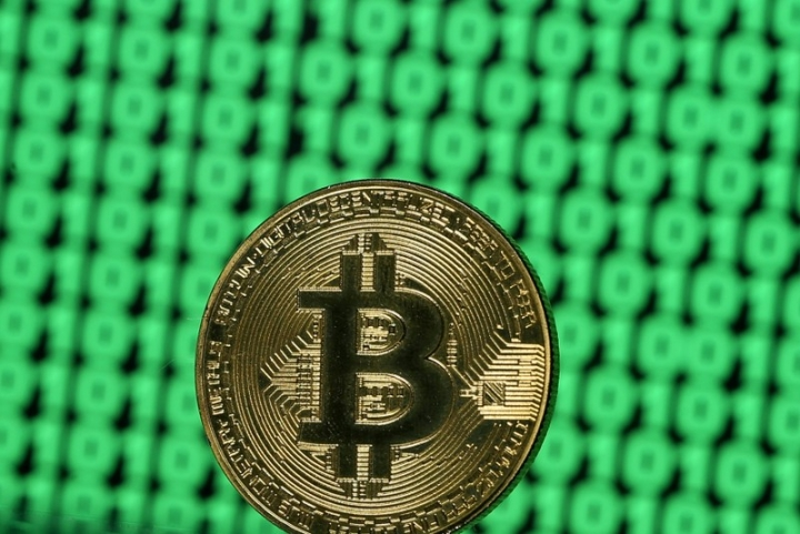 FILE PHOTO: A token of the virtual currency Bitcoin is seen placed on a monitor that displays binary digits in this illustration picture, December 8, 2017. REUTERS/Dado Ruvic//File Photo