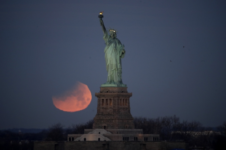 FILE - In this Jan. 31, 2018, file photo, the Statue of Liberty is backdropped by a supermoon, seen from the Brooklyn borough of New York. Workers will be turning off some lights for repairs to the Statue of Liberty's electrical system. The system that illuminates the statue's exterior will be shut down for about six hours on Tuesday night, May 15. However, the statue's torch, crown and pedestal will remain illuminated. (AP Photo/Julio Cortez, File)