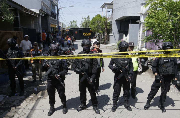 Police officers stand guard near the house of the family that carried the bombing of Surabaya police headquarters during a raid in Surabaya, Tuesday, May 15, 2018. The Indonesian family brought its 7-year-old daughter to the suicide bomb attack it launched Monday on the police headquarters in the country's second-largest city, authorities said, a day after members of another family conducted coordinated suicide bombings on three city churches that killed a number of people. (AP Photo/Achmad Ibrahim)