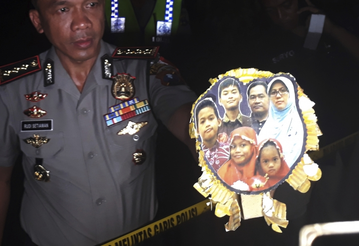 In this Sunday, May 13, 2018 file photo, Surabaya Police Chief Col. Rudi Setiawan shows a picture of the family of Dita Oepriarto who carried out the church attacks on Sunday, May 13, in Surabaya, East Java, Indonesia. The family fanned out on Sunday with suicide bombs attached to themselves and their children, attacking three churches. The entire family was killed in the attacks that killed a number of people and injured dozens of others. (AP Photo/Nanda Andrianta)