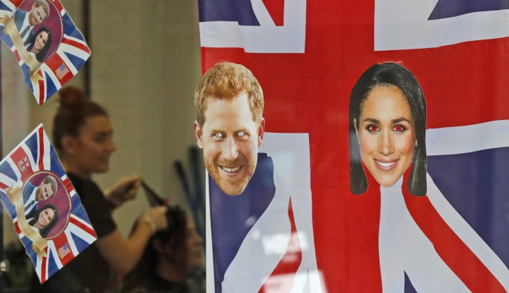 A woman gets a haircut as the shop window is decorated with flags and pictures of Britain's Prince Harry and Meghan Markle in Windsor, Tuesday, May 15, 2018. Preparations are being made in the town ahead of the wedding of Britain's Prince Harry and Meghan Markle that will take place in Windsor on Saturday May 19. (AP Photo/Frank Augstein)
