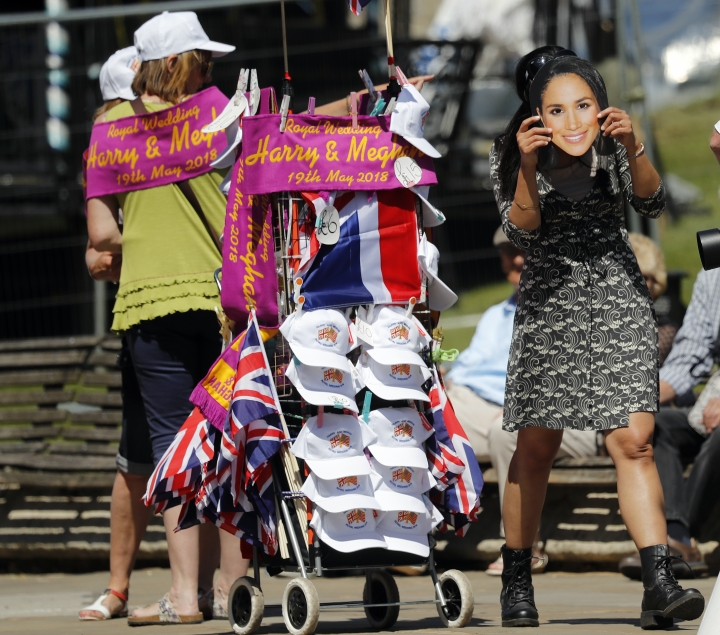 A woman uses a Meghan Markle mask, near a street vendor in Windsor, England, Tuesday, May 15, 2018. Preparations continue in Windsor ahead of the royal wedding of Britain's Prince Harry and Meghan Markle Saturday May 19. (AP Photo/Frank Augstein)