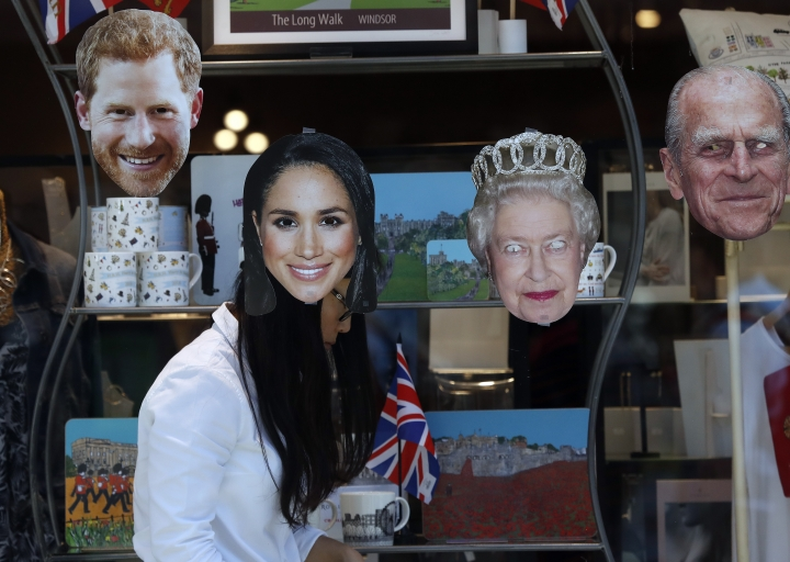 A shop assistant decorates a shop window in Windsor, England, Tuesday, May 15, 2018. Preparations continue in Windsor ahead of the royal wedding of Britain's Prince Harry and Meghan Markle Saturday May 19. (AP Photo/Frank Augstein)