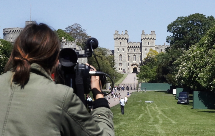 A camera woman films the Long Walk towards Windsor Castle in Windsor, England, on a sunny day Tuesday, May 15, 2018. Preparations continue in Windsor ahead of the royal wedding of Britain's Prince Harry and Meghan Markle Saturday May 19. (AP Photo/Frank Augstein)