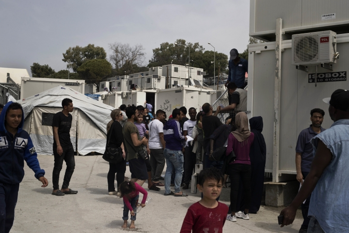 In this photo dated Friday, May 4, 2018 migrants and refugees wait outside UNHCR offices for their papers, inside the camp of Moria on Lesbos, Greece. Lawmakers in Greece are preparing Tuesday, May 15, to vote on draft legislation to speed up the asylum process for migrants and refugees and amend restrictions in an effort to ease overcrowding at camps on Greek islands. (AP Photo/Petros Giannakouris)
