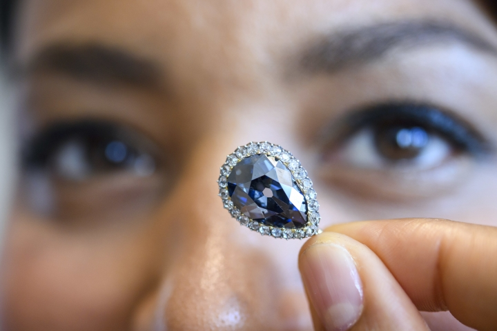 A Sotheby's employee displays The Farnese Blue during a preview at Sotheby's, in Geneva, Switzerland, Wednesday, May 9, 2018. One of the foremost Historic Diamonds The Farnese Blue emerges onto the market for the first time after three centuries in the same Family. Given to Elisabeth Farnese, Queen of Spain in 1715, The 6.16 carat diamond has passed down through four of Europe's most important royal families to ever appear at an auction. The auction will take place in Geneva on May 15, 2018. (Martial Trezzini/Keystone via AP)
