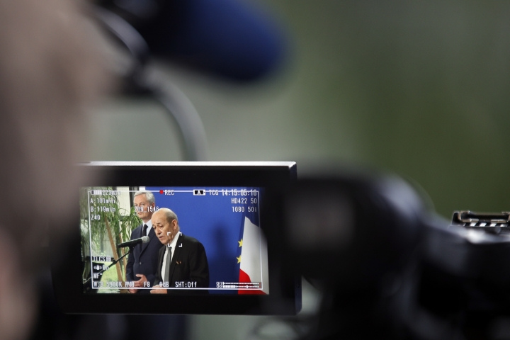 France's Finance Minister Bruno Le Maire, left, and Foreign Minister Jean-Yves Le Drian deliver their statement, pictured on a video viewer screen, at Bercy ministry, in Paris, Tuesday, May 15, 2018. Le Maire and Le Drian said they are determined to preserve the interests of French companies which have invested in Iran, following U.S. decision to withdraw from the Iran nuclear agreement and to impose tough economic sanctions on the country. (AP Photo/Francois Mori)