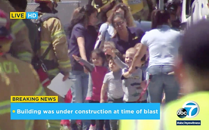 In this photo taken from video provided by KABC-TV, children are evacuated from a preschool across the street from a building that was rocked by an explosion in Aliso Viejo, Calif., Tuesday afternoon, May 15, 2018. None of these children were hurt. Authorities say one person is dead and several others have injuries. The cause of the blast is being investigated. (KABC-TV via AP)