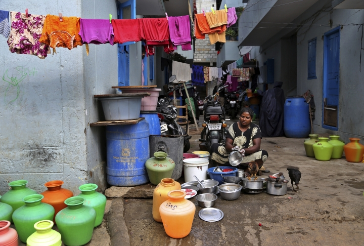 In this May 1, 2018 photo, a woman washes utensils outside her house in a poor residential neighborhood in Bangalore, India. India's Silicon Valley is bracing for yet another thirsty summer. Faucets are running dry and the lakes that once nurtured the southern city of Bangalore and its nearly 10 million residents are either parched or fetid with toxic effluents. Much like Cape Town in South Africa, Bangalore's water woes have been in the making for some time with years of unplanned urbanization, rapid population growth and poor management of water resources. (AP Photo/Aijaz Rahi)