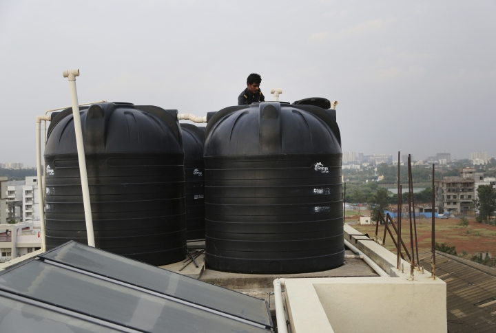 In this May 2, 2018 photo, a security guard checks the water level of tanks placed on top of a residential building in Bangalore, India. India's Silicon Valley is bracing for yet another thirsty summer. Faucets are running dry and the lakes that once nurtured the southern city of Bangalore and its nearly 10 million residents are either parched or fetid with toxic effluents. Much like Cape Town in South Africa, Bangalore's water woes have been in the making for some time with years of unplanned urbanization, rapid population growth and poor management of water resources. (AP Photo/Aijaz Rahi)