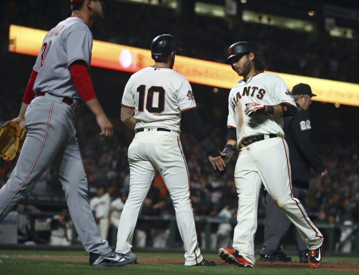 San Francisco Giants' Evan Longoria (10) and Brandon Crawford celebrate after scoring as Cincinnati Reds' Tyler Mahle, left, walks back to the mound during the fourth inning of a baseball game Tuesday, May 15, 2018, in San Francisco. Both scored on a single by Pablo Sandoval. (AP Photo/Ben Margot)