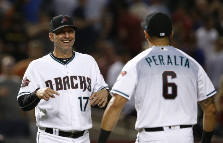Arizona Diamondbacks manager Torey Lovullo (17) smiles as he and David Peralta celebrate the team's 2-1 win over the Milwaukee Brewers in a baseball game Tuesday, May 15, 2018, in Phoenix. (AP Photo/Ross D. Franklin)