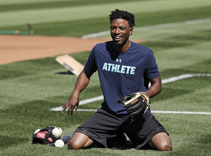 Seattle Mariners center fielder Dee Gordon smiles as he goes through a drill before the team's baseball game against the Texas Rangers Tuesday, May 15, 2018, in Seattle. Gordon could fill in at second base while Robinson Cano is out for 80 games on suspension for violating baseball's joint drug agreement. (AP Photo/Elaine Thompson)