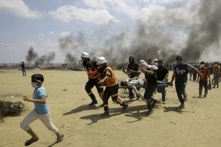 FILE - In this Monday, May 14, 2018 file photo, Palestinian medics and protesters evacuate a wounded youth during a protest at the Gaza Strip's border with Israel, east of Khan Younis, Gaza Strip. Arab states resoundingly condemned the killing of more than 50 Palestinians on Monday, May 14, 2018 in Gaza protests, just as they have after previous Israeli violence going back decades. But behind the scenes, fears over Iran have divided Arab leaders, with some willing to quietly reach out to Israel. (AP Photo/Adel Hana, File)