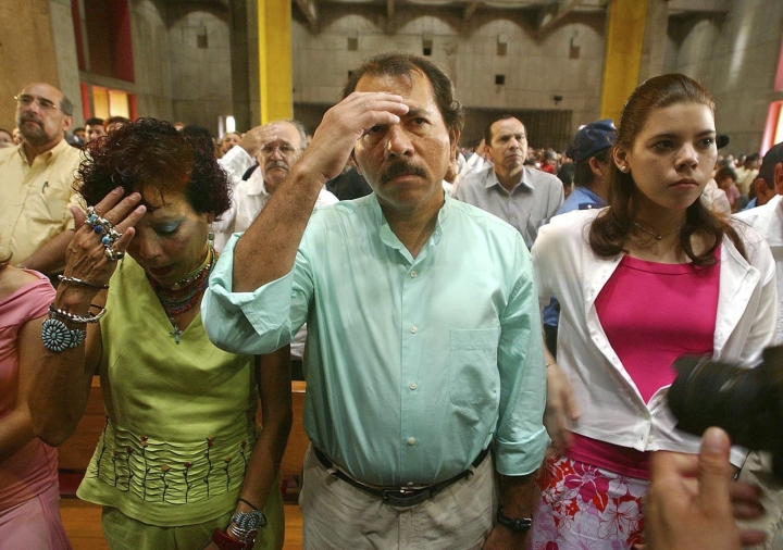 FILE - In this July 19, 2004 photo, Daniel Ortega, then former president of Nicaragua, his partner Rosario Murillo, left, make the sign of the cross, accompanied by their eldest daughter Camila, during a Mass for those who fell during the Sandinista revolution, in Managua, Nicaragua. As the relationship between Ortega and the Catholic Church began to thaw, his longtime foe Cardinal Miguel Obando y Bravo presided over the marriage of Ortega and Murillo in 2005. (AP Photo/Esteban Felix, File)