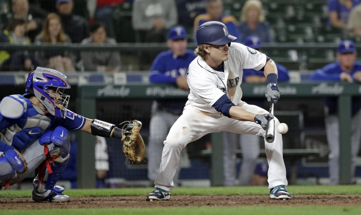 Seattle Mariners' Gordon Beckham lays down a sacrifice bunt as Texas Rangers catcher Robinson Chirinos looks on in the eighth inning of a baseball game Tuesday, May 15, 2018, in Seattle. Beckham was safe at second on a throwing error by pitcher Jose Leclerc and one run scored. (AP Photo/Elaine Thompson)