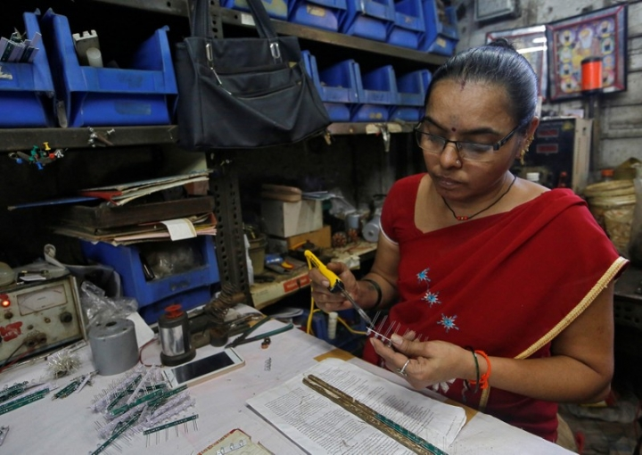 A woman solders LED bulbs onto a grid to make indicator lights inside an electrical manufacturing unit in Mumbai, India March 22, 2018. Picture taken March 22, 2018. REUTERS/Francis Mascarenhas
