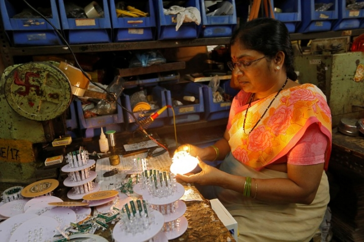 A woman tests LED bulbs after installing them onto a grid to make indicator lights inside an electrical manufacturing unit in Mumbai, India March 22, 2018. Picture taken March 22, 2018. REUTERS/Francis Mascarenhas