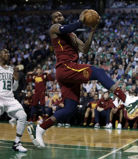 Cleveland Cavaliers forward LeBron James recoils after colliding with Boston Celtics forward Jayson Tatum, out of picture, in front of Celtics guard Terry Rozier, left, during the first half in Game 2 of the NBA basketball Eastern Conference finals, Tuesday, May 15, 2018, in Boston. (AP Photo/Charles Krupa)