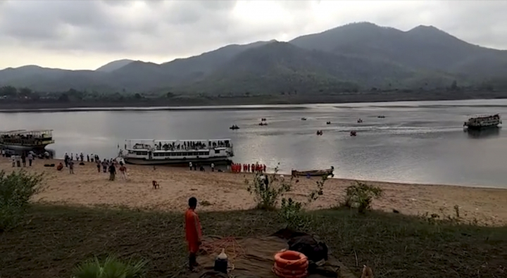 In this image made from video provided by K.K.Productions, rescuers on rafts search in the Godavari River after a ferry capsized in heavy winds Tuesday in Devipatnam, Andhra Pradesh state, India, Wednesday, May 16, 2018. Anywhere from 10 to 40 people are reported missing. (K.K.Productions via AP)
