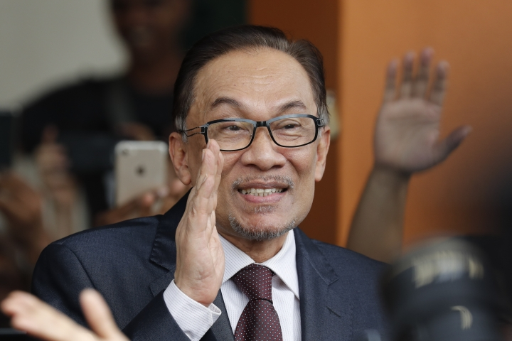 Malaysia jailed opposition icon Anwar Ibrahim waves to supporters as he leaves a hospital in Kuala Lumpur, Malaysia, Wednesday, May 16, 2018. Prime Minister Mahathir Mohamad said Malaysia's king had agreed to pardon Anwar, who was jailed in 2015 for sodomy in a conviction that he said was politically motivated. (AP Photo/Vincent Thian)