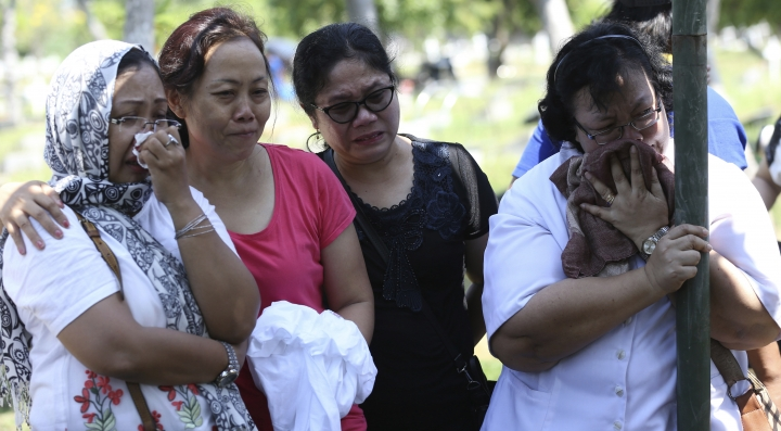 Relatives of Marta Djumani, a victim in last Sunday's church attacks, cry during her funeral in Surabaya, East Java, Indonesia, Wednesday, May 16, 2018. Family members sow flowers for Marta Djumani, one of the victims of Sunday's church attacks, during funeral at cemetery in Surabaya, East Java, Indonesia, Wednesday, May 16, 2018. Indonesian police fatally shot a militant and arrested 13 others Tuesday suspected of links to suicide bombings carried out by two families in the country's second-largest city. Coordinated suicide bombings at three churches were carried out Sunday by a family of six that included girls aged 8 and 12. (AP Photo/Achmad Ibrahim)