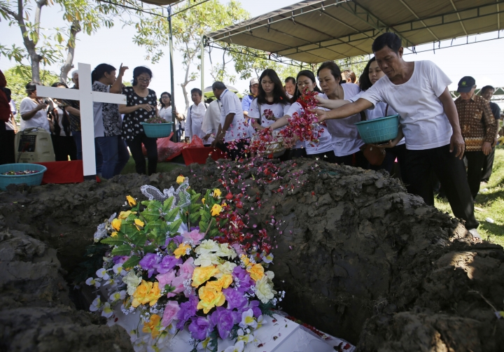 Family members sprinkle flower pedals over the coffin of Marta Djumani, one of the victims of Sunday's church attacks, during a funeral in Surabaya, East Java, Indonesia, Wednesday, May 16, 2018. Indonesian police fatally shot a militant and arrested 13 others Tuesday suspected of links to suicide bombings carried out by two families in the country's second-largest city. Coordinated suicide bombings at three churches were carried out Sunday by a family of six that included girls aged 8 and 12. (AP Photo/Achmad Ibrahim)