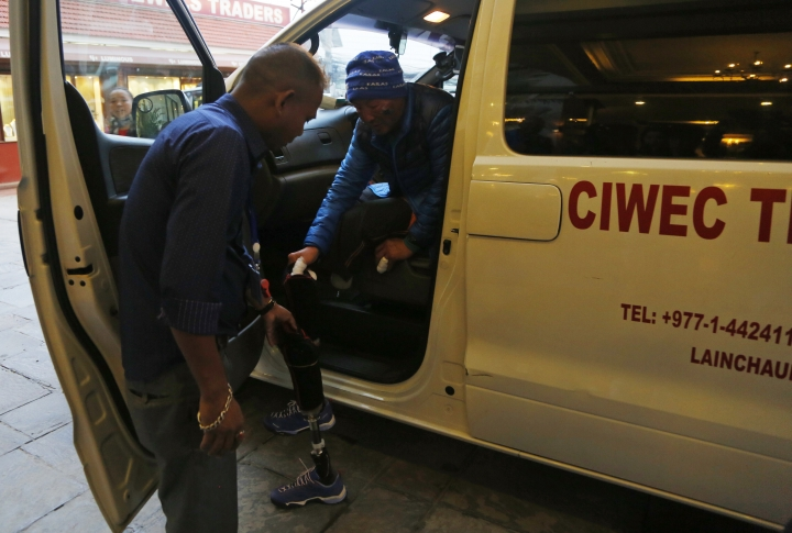 Chinese climber Xia Boyu, 69, gets out from an ambulance as he arrives in a hotel in Kathmandu, Nepal, Wednesday, May 16, 2018. Boyu, who lost both his feet while trying to reach summit, has successfully climb Everest on his fifth attempt. (AP Photo/Niranjan Shrestha)
