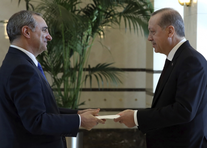 FILE - In this Dec. 5, 2016 file photo, Turkey's President Recep Tayyip Erdogan, right, and the new Israeli Ambassador Eitan Naeh speak as Naeh presents his letter of credentials, in Ankara, Turkey. Turkey on Tuesday temporarily expelled Israel's ambassador in Ankara after he was called into the ministry, where Turkey relayed its condemnation of Israel's use of deadly force on Gaza protesters. (AP Photo/Burhan Ozbilici, File)