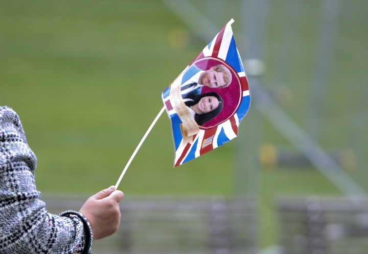 A tour guide leads her group of tourists using a flag with the faces of Britain's Prince Harry and his fiance Meghan Markle in Windsor, England, Wednesday, May 16, 2018. Preparations continue in Windsor ahead of the royal wedding of Britain's Prince Harry and Meghan Markle Saturday May 19. (AP Photo/Alastair Grant)